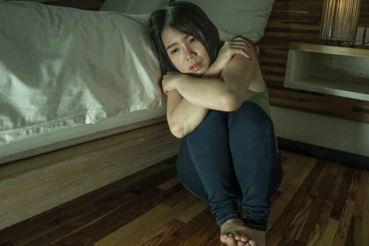 young depressed and sad Asian Korean woman sitting on floor at bedroom next to bed suffering depression problem and anxiety crisis feeling desperate